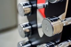 Closeup image of chrome dumbbells. In modern gym Royalty Free Stock Image