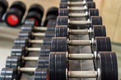 Closeup image of chrome dumbbells. In modern gym Royalty Free Stock Photos