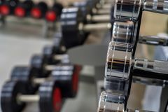 Closeup image of chrome dumbbells. In modern gym Royalty Free Stock Photography
