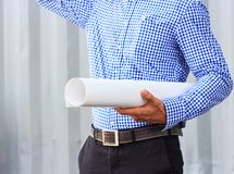 Closeup image of construction engineer holding blueprints at bui. Lding site Stock Images