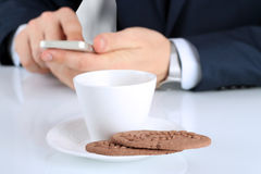 Closeup image of Cup of coffee with cookies .Businessman holdin Royalty Free Stock Photo