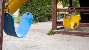 Closeup image of empty swings on children playground at park. Closeup photo of empty swings on children playground at park Royalty Free Stock Images