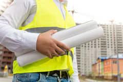 Closeup image of engineer in safety vest holding rolled blueprints stock image