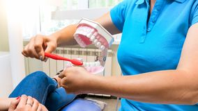 Closeup image of female dentist explaining her patient importance of teeth hygiene. Closeup photo of female dentist explaining her patient importance of teeth Stock Photo