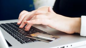Closeup photo of female hands typing on keyboard. Credit card lying on laptop. Closeup image of female hands typing on keyboard. Credit card lying on laptop royalty free stock image