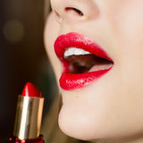 Closeup image on glamor charming beautiful girl lips & white teeth with gorgeous makeup draws red lipstic Royalty Free Stock Image