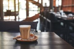 A glass of hot coffee on wooden table in cafe stock photo