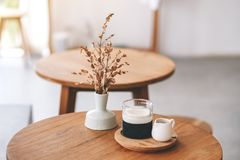 A glass of latte coffee on wooden table in minimal cafe. Closeup image of a glass of latte coffee on wooden table in minimal cafe stock photography
