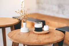 A glass of latte coffee on wooden table in minimal cafe. Closeup image of a glass of latte coffee on wooden table in minimal cafe stock photo
