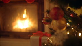 Closeup image of golden and red baubles on Christmas tree. Burning fireplace on the background. stock footage