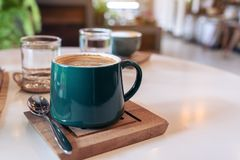Green mugs of hot coffee and glasses of water on table in cafe. Closeup image of green mugs of hot coffee and glasses of water on table in cafe royalty free stock photography
