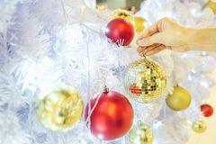 Closeup image of a hand decorating white snow Christmas tree with gold sparkling glitter baubles, disco crystal ball style. Concept and idea of celebrating Stock Image