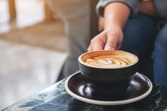A hand holding a cup of hot coffee on table. Closeup image of a hand holding a cup of hot coffee on table stock images
