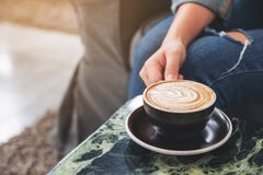 A hand holding a cup of hot coffee on table. Closeup image of a hand holding a cup of hot coffee on table stock photos