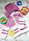 Closeup image of hand knitted child's hat & cardigan surrounded with toys on light copy space background Royalty Free Stock Photos