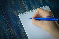 Closeup image of hand writing down on a blank. Top view of female hands making some notes work, studying, shopping, blogging conce. Pt royalty free stock photo