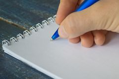 Closeup image of hand writing down on a blank. Top view of female hands making some notes work, studying, shopping, blogging conce. Pt royalty free stock photos