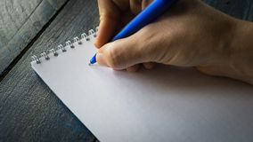 Closeup image of hand writing down on a blank. Top view of female hands making some notes work, studying, shopping, blogging conce. Pt stock photography