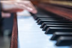 Hands playing a vintage wooden grand piano royalty free stock image
