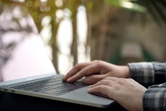 Closeup image of hands working , touching and typing on laptop keyboard with blur nature Stock Images