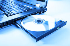 Closeup image of a laptop and a CD / DVD disc Royalty Free Stock Images