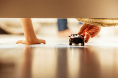 Closeup image little boy hands with toy car. Boy playing with toy car overhang from the bed Stock Image