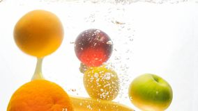 Closeup image of lots of tasty fresh juicy fruits falling in water and splashing. Closeup photo of lots of tasty fresh juicy fruits falling in water and royalty free stock photography