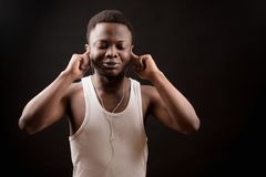 Closeup image of male with dark skin listening to favourite band. Concentrating on music. pleasant song.music lover Royalty Free Stock Images
