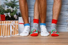 Closeup image of male feet in woolen socks on a wooden background. Hairy men`s legs in New Year`s socks. royalty free stock photography