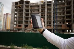 Closeup image of male hand holding digital tablet against building under construction. Closeup photo of male hand holding digital tablet against building under Stock Photo