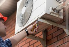 Closeup image of male worker installing air conditioner unit. Closeup photo of male worker installing air conditioner unit Royalty Free Stock Photography