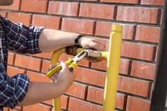 Closeup image of male worker installing pressure valve on yellow gas pipes royalty free stock photography