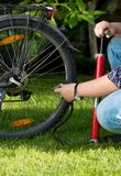 Closeup image of man connecting air pump to valve on bicycle wheel stock images