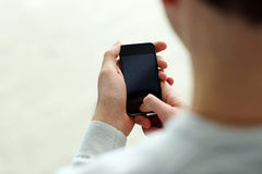 Closeup image of a man holding smartphone and looking at display Stock Images