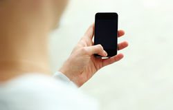 Closeup image of a man looking at blank smartphone display Stock Images