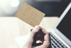Closeup Image Man Showing Blank Craft Business Card and Using  Modern Laptop on Wood table Blurred Background. Mockup. Ready for Private Information. Sunlight Royalty Free Stock Photos