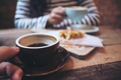 A man and a woman holding and drinking hot coffee together with a piece of raisin danish on wooden vintage table in coffee shop royalty free stock images