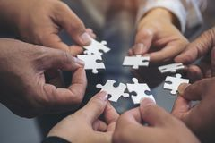 Many people hands holding a jigsaw puzzle in circle together. Closeup image of many people hands holding a jigsaw puzzle in circle together stock photo