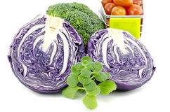 Closeup image mix of raw and fresh vegetables.purple cabbage, cherry tomatoes on trolley, green mint and broccoli. Isolated white background Stock Photos