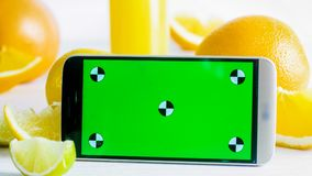 Closeup photo of mobile phone with green chromakey screen next to fresh fruits on white table. Perfect for inserting stock photography