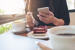 Free Closeup Image Of A Woman Holding , Using And Looking At Smart Phone While Eating A Cake With White Coffee Cups And Laptop Stock Photos - 104894113
