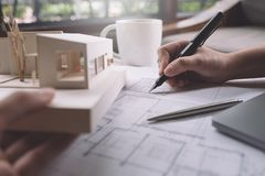 Free Closeup Image Of Architects Drawing Shop Drawing Paper With Architecture Model Royalty Free Stock Image - 105612576