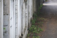 Closeup image of an old white concrete fence wall with blur green nature Stock Image