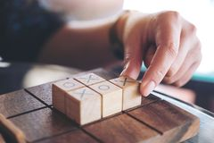 People playing wooden Tic Tac Toe game or OX game. Closeup image of people playing wooden Tic Tac Toe game or OX game Royalty Free Stock Photos