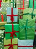 Closeup image of pile of lots of Christmas gifts. Stack of green boxes with red ribbons with New Year presents. Closeup photo of pile of lots of Christmas gifts royalty free stock photos