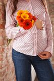 Closeup image of pregnant woman touching her belly with hands. Young pregnant woman holding bunch of bright summer flowers royalty free stock photography