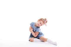 Closeup image of a pretty little girl sitting on the floor. Closeup image of a pretty little girl sitting on the floor on a white background Stock Photo