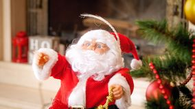 Closeup image of Santa Claus miniature under Christmas tree stock images