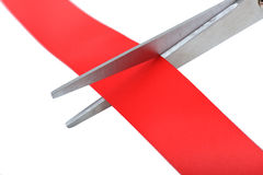 A Closeup image of scissors cutting a red ribbon. Stock Photos