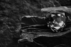 A Closeup Image of a Single Gem Stone Showing the Facets of the Gem on a Rock. A Black and White Photo of a Single Gem Stone, with a Blurred Rock Background stock photo